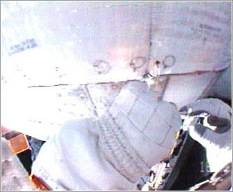 John (Danny) Olivas grapando la manta en su sitio © NASA TV