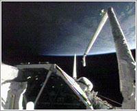 Canadarm a punto de coger el OBSS © NASA TV