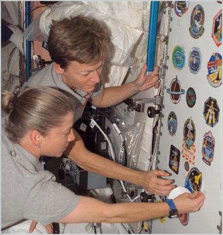 Pam Melroy y Peggy Whitson colocan el escudo de la misión STS-120 en el módulo Unity / NASA