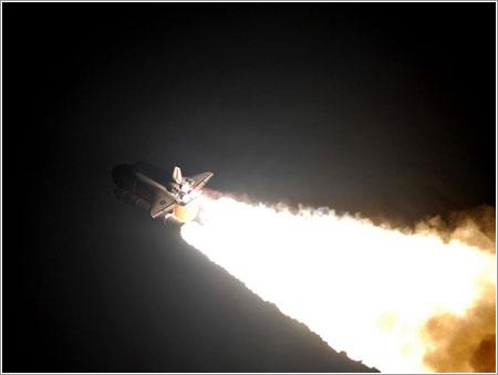 El Endeavour sobre la columna de fuego de su lanzamiento - NASA/Jerry Cannon, Rusty Backer