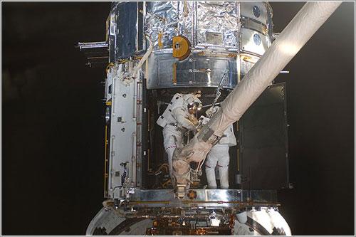 Mike Massimino y Michael Good trabajando en el interior del Hubble