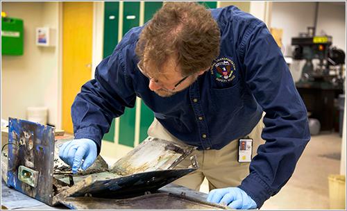 Técnico de la NTSB inspeccionando los restos de la batería