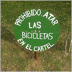 Cartel: «Prohibido atar las bicicletas en el cartel»